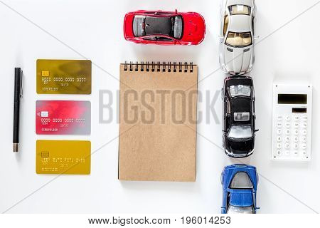 Choosing car concept. Toy cars and bank card on white background top view.