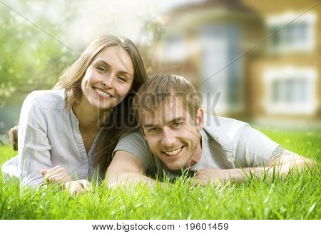 Happy Couple near their Home.Smiling Family outdoor.Real Estate