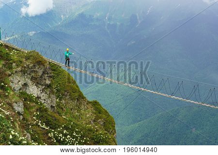 A Tourist In A Helmet And Safety Ropes Is Tight Between The Rocks Stairs