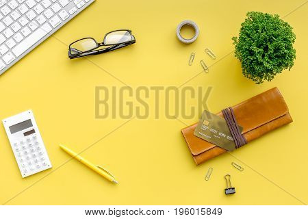 Concept of paying by credit card online. Bank card nearby keyboard on yellow table background top view.