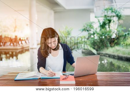 Young Girl Student Serious Writing with School Folders Book and Laptop in Education Campus University Outdoor