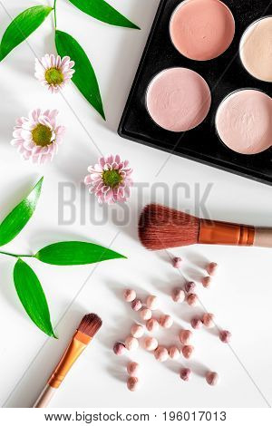 Cosmetics. Eyeyeshadow palette and brush on white table background top view.
