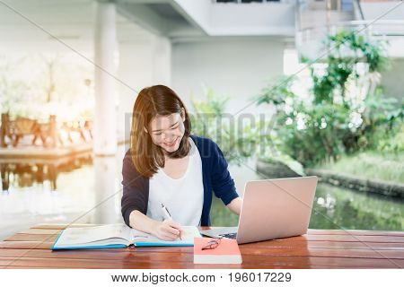 Young Girl Student Smiling Writing with School Folders Book and Laptop in Education Campus University Outdoor