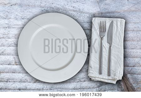Empty plate with silverware on gray background.