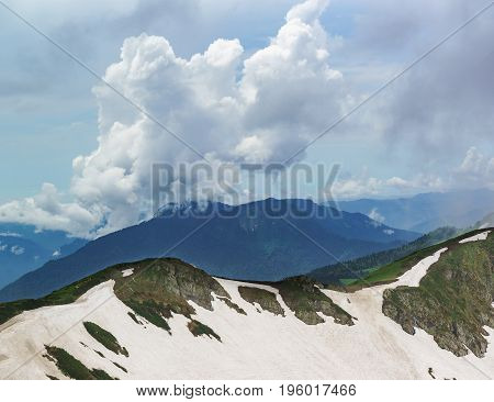 Clouds Over The Snow-covered Aibga Ridge In Cloudy Summer Day