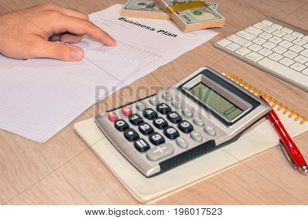 Close up view of bookkeeper or financial inspector hands making report calculating or checking balance. Business plan calculator dollar banknote on the table - color / Old Polaroid