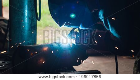 Welder uses torch to make sparks during repair exhaust pipe auto