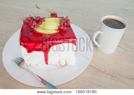 A cup of coffee and cake on wooden background. piece cake on white plate with fork