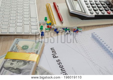 Close up view of bookkeeper or financial inspector hands making report calculating or checking balance. Business plan calculator dollar banknote on the table