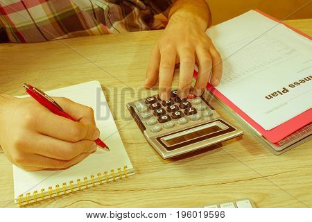 Close up Man hand using calculator and writing make note with calculate about cost at home office. Business concept. The Man and computer are using a calculator on the table in the office room - Retro color