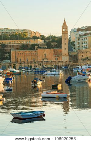 View to marina with colorful boats at sunrise, Malta