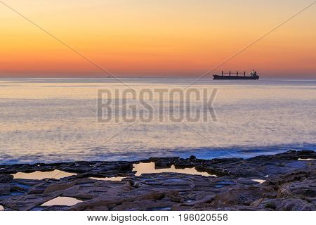 Silhouette of the boat at sunrise in the sea