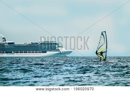 Windsurfer in the sea with cruise ship on backgroung