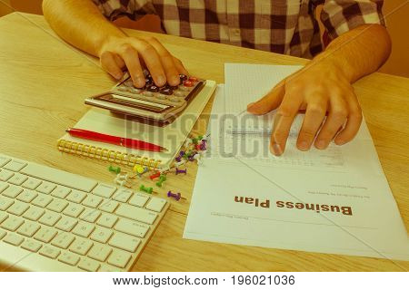 Businessman working on office desk with Calculator. accounting concept. Financial report values with dollars calculator - Retro color