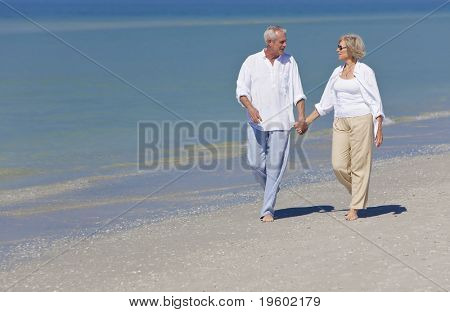 Happy senior man and woman couple together holding hands and walking on a deserted tropical beach