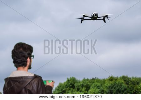 Young man playing with the drone in a blue sky by using a controller.