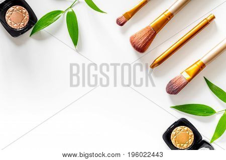 Makeup tools. Brushes and eyeshadows on white table background top view copyspace.