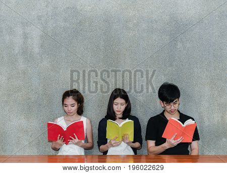 Young Students Group Smiling Looking School Folders Book on Table and Gray Background in Education Campus University