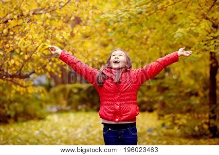 very happy teenage girl in the park in autumn with yellow leaves. adolescent with arms outstretched outdoor