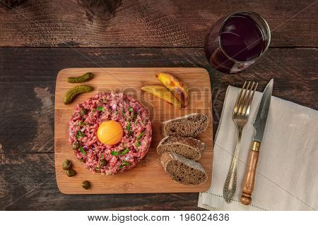A photo of a steak tartare with a raw egg yolk, gherkins, capers, rye bread, roasted potatoes, a glass of red wine, a fork, and a knife, shot from above on a dark rustic texture with a place for text