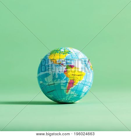 Travel theme with miniature world globe on a green background
