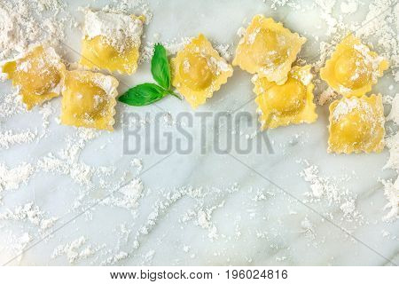 An overhead photo of ravioli with flour and basil leaves, shot from above on a white marble table with a place for text