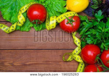 A Healthy Diet, Fresh Vegetables, Greens And A Measuring Tape On A Wooden Table. Top View With Copy
