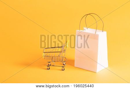 Retail shopping theme with gift bag with shopping cart on a yellow background
