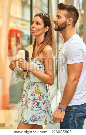 A beautiful young tourist couple are talking on the street next to a shops window in Budapest, Hungary.