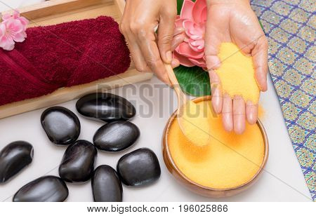 Spa therapist is putting scrubbing salt on her hand with other objects