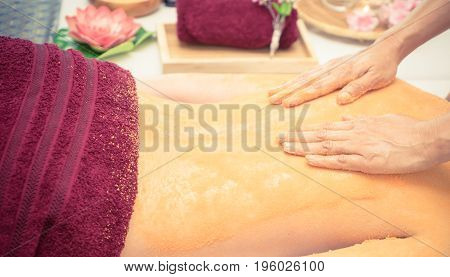 Spa Therapist is scrubbing customer back with orange salt
