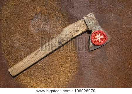 Old ax with a slice of ripe tomato