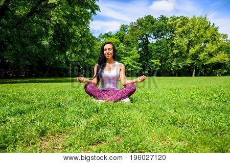 A beautiful young sporty girl sitting and meditating on the grass in a park, wearing a leggings and a top