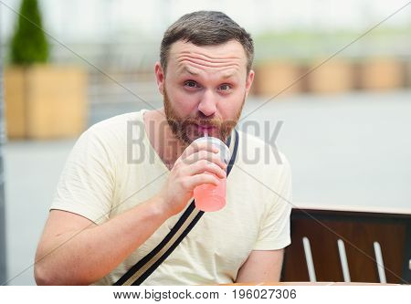 Man With A Beard Drinks A Soft Drink In The City.