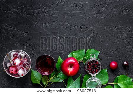 Fruits and berries for summer fruit drink on black stone table top view.