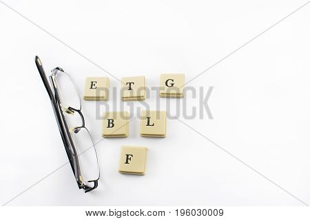 Black eyeglasses with brown letters on a white background