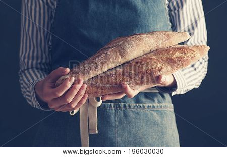 Baker's hands hold fresh baguettes over dark background