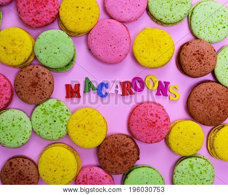 Multicolored macaroons on a pink background in the middle the inscription is made of small wooden letters of macaroons