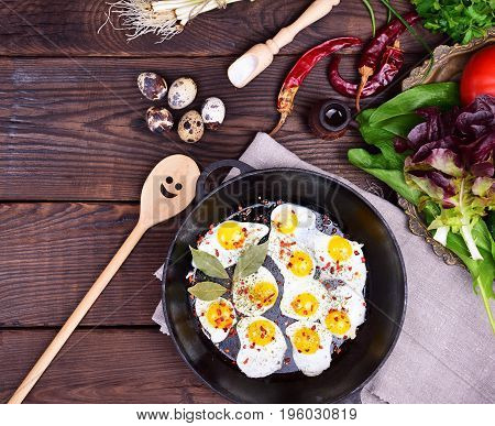 Fried quail eggs in a cast-iron frying pan and fresh vegetables top view