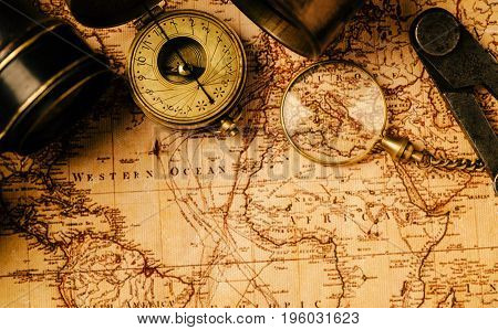 Vintage still life. Old vintage retro compass and spyglass on ancient world map. Travel geography navigation concept background. Top view. poster