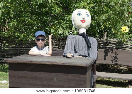 Child with big doll sitting at table