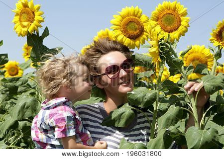 Happy mother with her son among sunflowers