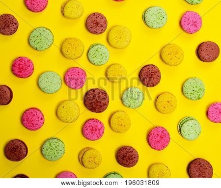 Colorful pastry macarons on a yellow background abstract background