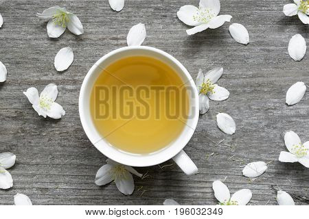 Jasmine tea and Jasmine flowers on rustic wooden background. top view