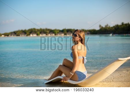 Young woman relaxing in a modern deck chair on a tropical beach. Girl is sitting on a beach sun bed chilling near ocean, palms and bungalows on Maldives. Vacation concept
