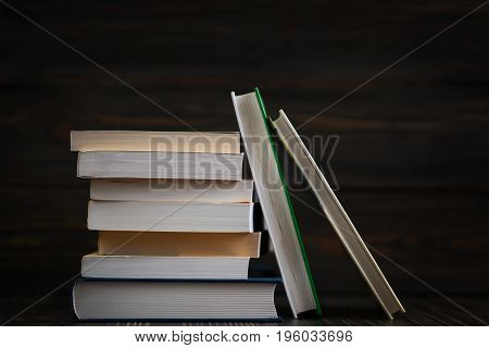 Education concept. Stack of books close up with rustic wooden background.