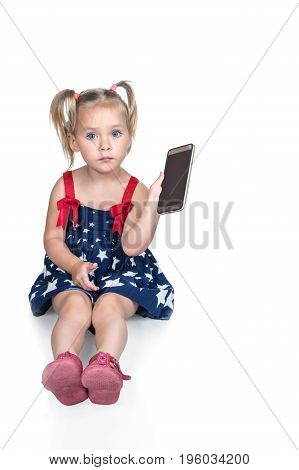 Little beautiful girl in a dress sits on the floor and holds a smartphone in her hand, isolated on a white background