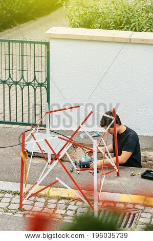 PARIS FRANCE - JUL 12 2017: Young worker inside sewage manhole hole - telecommunication internet provider company working on implementation of fiber optic cables in sewage system using fiber optic welding machine to cover the whole Paris area