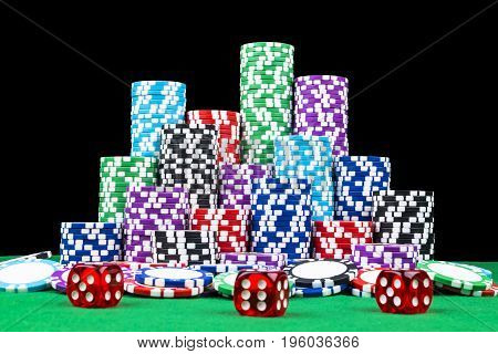 Stack of Poker chips on a green gaming poker table with poker dice at the casino. Playing a game with dice. Casino dice Concept for business risk chance good luck or gambling. chips and dice for poker