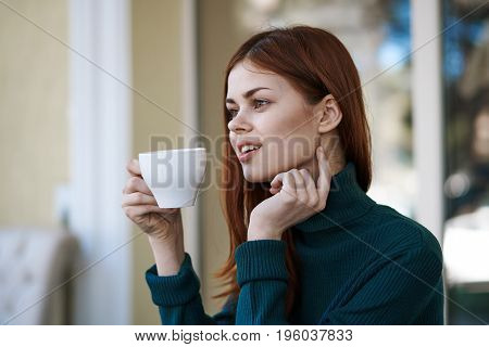 Young beautiful woman drinks coffee in a cafe.